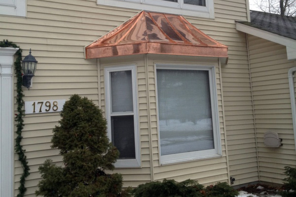 copper bay window roof on house with yellow siding